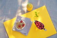 Den sunda frukosten med glass hemlagad granola med yoghurt och nya bärhallon i silver bowlar den nya mintkaramellen för orange fr arkivbild