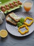 Den sunda frukosten med hemmet gjorde bröd och ägg och orange fruktsaft på den gråa plattan och grått bakgrundsideal för kulinari arkivbild