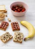 Den sunda frukosten med ingredienser, bantar begrepp Strikt vegetarianrostade bröd med frukter, frö, jordnötsmör på en vit träbak arkivbilder