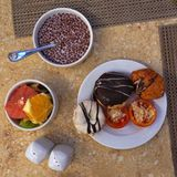 Den sunda frukosten med mjölkar, mysli, donuts och frukter, på en träbakgrund Top beskådar royaltyfri fotografi