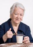 Den sunda gamla kvinnan med ett exponeringsglas av mjölkar Arkivbilder
