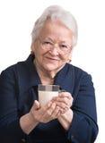 Den sunda gamla kvinnan som rymmer ett exponeringsglas av, mjölkar Royaltyfria Foton