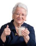 Den sunda gamla kvinnan som rymmer ett exponeringsglas, mjölkar Arkivbild