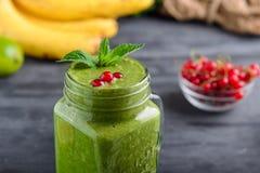 Den sunda gröna spenatsmoothien i en krus rånar dekorerat med bär för mintkaramellen och för den röda vinbäret med ingredienser p Fotografering för Bildbyråer