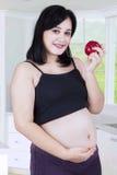 Den sunda gravida kvinnan rymmer äpplet Royaltyfri Fotografi