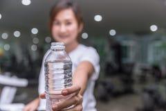 den sunda hållen för handen för konditionflickaleendet ger vattenflaskan av dricksvatten royaltyfri fotografi