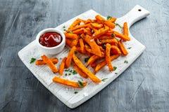 Den sunda hemlagade bakade orange sötpotatisen steker med ketchup som är salt, peppar på det vita träbrädet Royaltyfri Fotografi