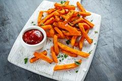 Den sunda hemlagade bakade orange sötpotatisen steker med ketchup som är salt, peppar på det vita träbrädet arkivbild