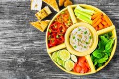 Den sunda hemlagade läckra kryddiga hummusen med behandla som ett barn morötter, selleripinnar, spenat, ingefäran, peppar, skivad Arkivfoto
