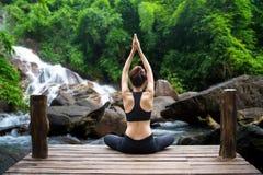 Den sunda kvinnalivsstilen balanserade övning mediterar och zenenergiyoga på bron i morgon vattenfallet i naturskog royaltyfri bild