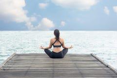 Den sunda kvinnalivsstilen mediterar allsidig yogaövning och energi på bron arkivfoto