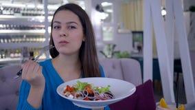 Den sunda kvinnan bantar, den lyckliga flickan som äter härlig hälsosam sallad från den stora plattan, medan äta middag grönsaklu lager videofilmer