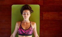Den sunda kvinnan i savasana poserar på idrottshallen Royaltyfria Bilder
