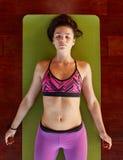 Den sunda kvinnan i savasanayoga poserar på idrottshallen Royaltyfri Bild