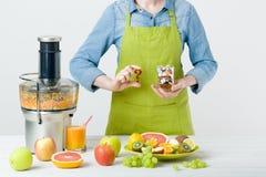 Den sunda livsstilen och bantar begrepp Fruktfruktsaft, preventivpillerar och vitamintillägg, kvinna som gör ett val Royaltyfria Bilder