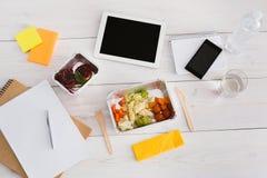 Den sunda lunchfolieasken med bantar mat på kontorstabellen Royaltyfri Bild