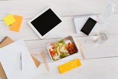 Den sunda lunchfolieasken med bantar mat på kontorstabellen Royaltyfria Foton