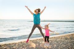 Den sunda modern och behandla som ett barn flickabanhoppning på stranden Royaltyfri Fotografi