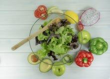 Den sunda salladbunken på vit träbakgrund, har sund sallad för lunchtid att banta mat, vegetarian bantar, mat och hälsobegreppet royaltyfri fotografi