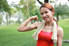 Den sunda starka asiatiska kvinnan i den röda sportswearen som visar hennes händer i naturligt, parkerar Kondition- och livsstilb royaltyfri fotografi
