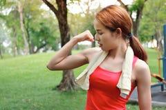 Den sunda starka asiatiska kvinnan i den röda sportswearen som visar hennes händer i naturligt, parkerar Kondition- och livsstilb arkivfoto