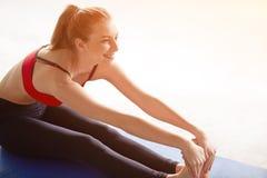 Den sunda unga idrottskvinnan gör övningarna som sitter med raka ben Arkivbilder