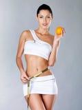 Den sunda unga kvinnan med att mäta tejpar och apelsinen Arkivbilder