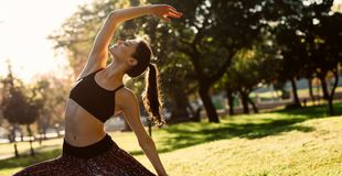 Den sunda unga kvinnan som tillbaka böjer och sträcker på, parkerar Kvinnlig praktiserande sträckande yogadet fria i morgon arkivfoto