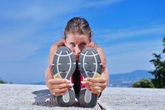 Den sunda unga nätta kvinnan som sträcker hennes ben under övning parkerar in arkivbilder