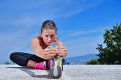 Den sunda unga nätta kvinnan som sträcker hennes ben under övning parkerar in royaltyfri fotografi
