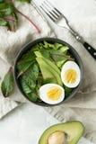 Den sunda vegetariska frukosten bowlar med sallad, avokadot och ägget, bästa sikt Rent äta, bantar matbegrepp Arkivbilder