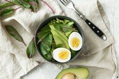 Den sunda vegetariska frukosten bowlar med sallad, avokadot och ägget, bästa sikt Rent äta, bantar matbegrepp Arkivfoto