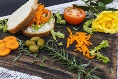 Den sunda vegetariska smörgåsen med moroten, tomaten, grönsallat och kryddor, tjänade som på ett träbräde, med en gul ros royaltyfria foton