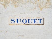 Den Suquet gataskylten på en vit stenar väggen alella de Palafrugell, Spanien royaltyfria bilder