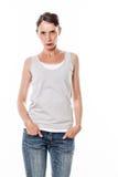 Den sura härliga unga kvinnan med händer i jeans stoppa i fickan arkivfoto