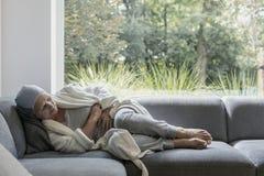 Den svaga äldre kvinnan med cancer och magen smärtar bara hemma arkivbilder