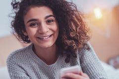 Den svartögda unga kvinnan som har ansiktsbehandlingen, rynkar att le i huvudsak royaltyfri foto