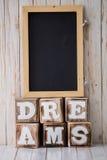 Den svart tavlan och DRÖMMAR undertecknar gjort av träkvarter på träbackg Royaltyfri Fotografi