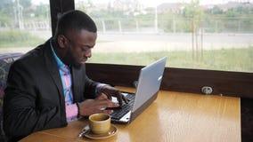 Den svarta affärsmannen arbetar skriva ett meddelande på bärbara datorn som sitter i sommarkafé arkivfilmer