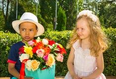 Den svarta afrikansk amerikanpojkeungen ger blommor till flickabarnet på födelsedag Små förtjusande barn parkerar in Arkivfoto