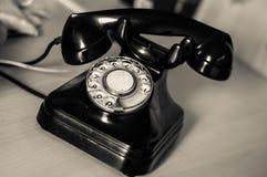 Den svarta antika telefonen på tabellen Royaltyfri Foto
