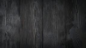 Den svarta bakgrunden av träbräden Arkivbild