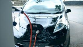 Den svarta bilen får laddad med elektricitet lager videofilmer