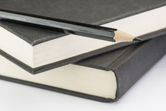 Den svarta blyertspennan på svart två skriver böcker royaltyfri fotografi