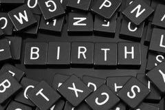 Den svarta bokstaven belägger med tegel att stava ordet & x22en; birth& x22; arkivbild
