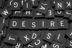 Den svarta bokstaven belägger med tegel att stava ordet & x22en; desire& x22; royaltyfri fotografi