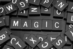 Den svarta bokstaven belägger med tegel att stava ordet & x22en; magic& x22; arkivbild