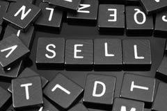 Den svarta bokstaven belägger med tegel att stava ordet & x22en; sell& x22; royaltyfri foto
