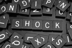 Den svarta bokstaven belägger med tegel att stava ordet & x22en; shock& x22; royaltyfri fotografi