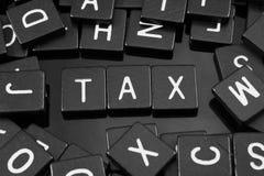 Den svarta bokstaven belägger med tegel att stava ordet & x22en; tax& x22; royaltyfria foton